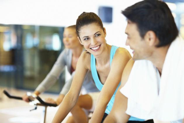 man talking to woman in spin class