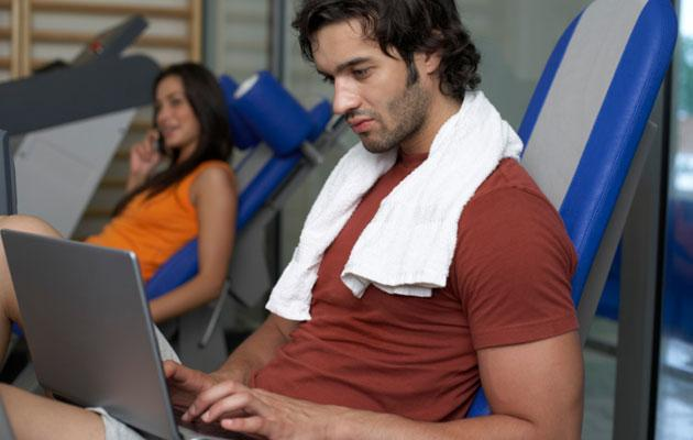 Man on Laptop at Gym