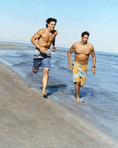 Two Men Barefoot Running on Beach