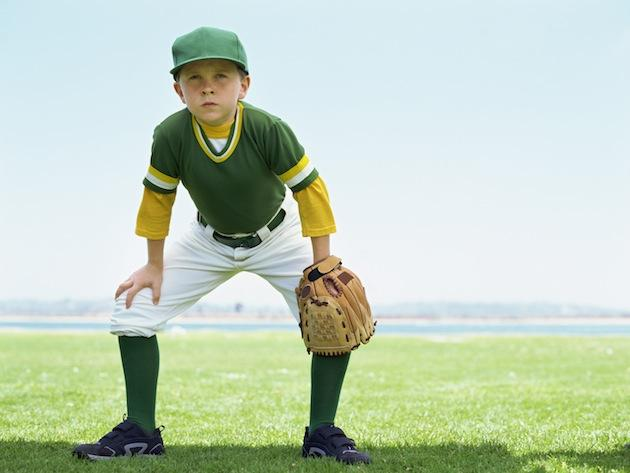 young boy playing baseball in a field