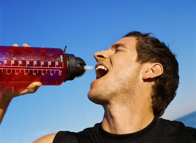man drinking out of water bottle