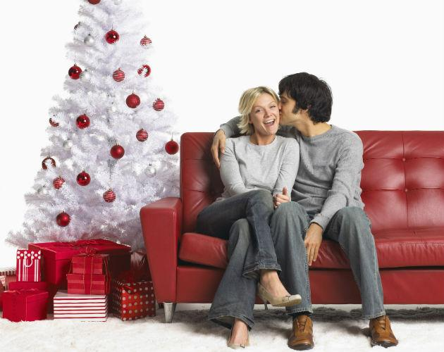 young couple sitting by christmas tree