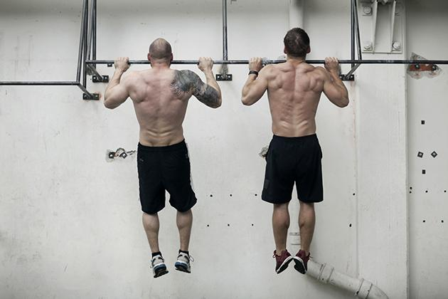 two men doing pullups at a CrossFit gym