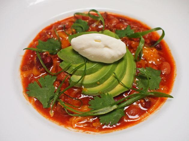 bowl of chili with avocado and sour cream