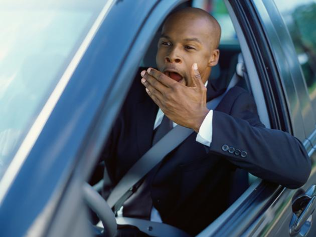 man yawning while driving a car