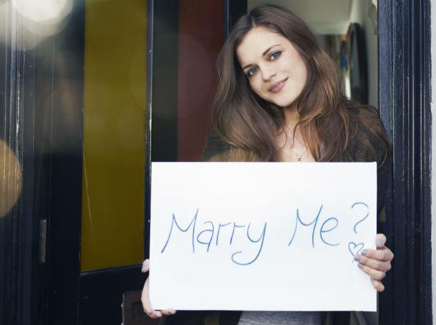 woman holding marry me sign