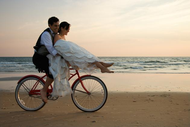 bride and groom riding bike on beach
