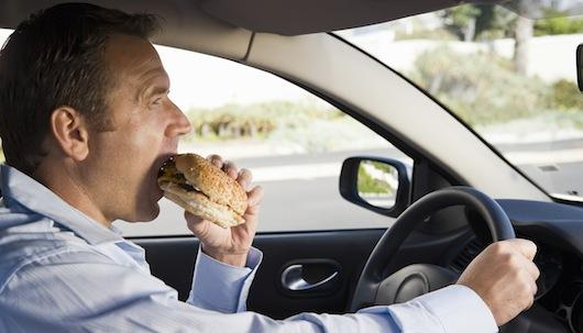 man eating fatty fast food in his car