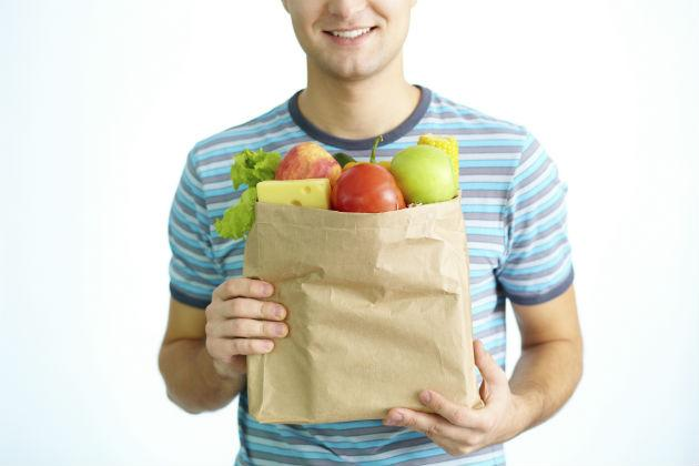 young man holding bag of fruits and vegetables