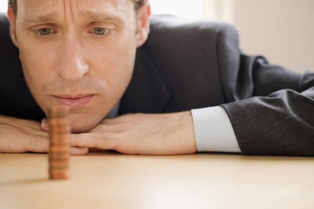 man staring at stack of coins