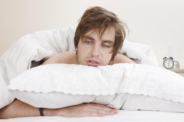 man suffering from lack of sleep resting head on a pillow