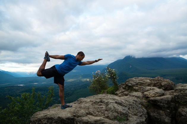 man doing yoga on a mountain