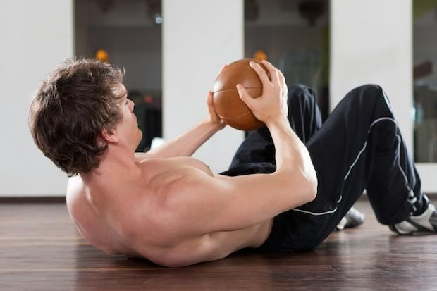Man doing sit ups with a medicine ball
