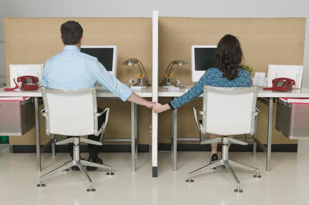 man and woman holding hands at work