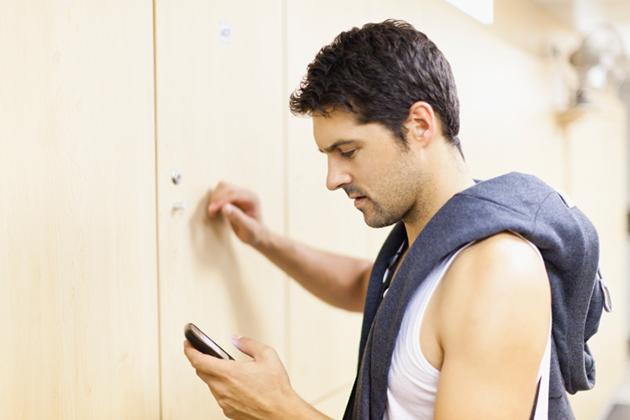 man using smartphone at the gym