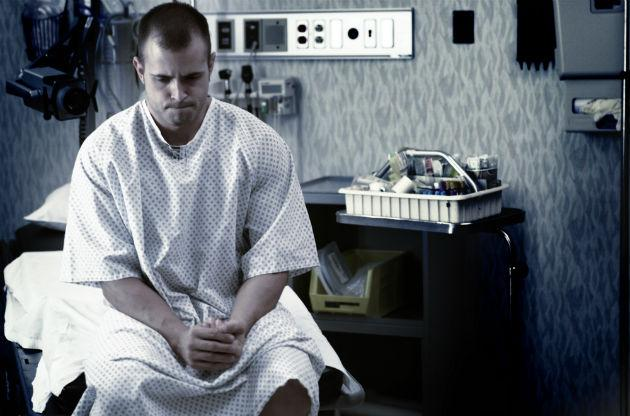 man waiting in hospital gown