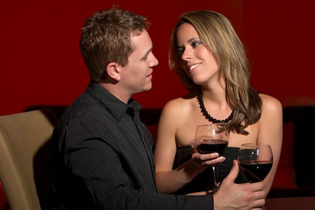 man and woman flirting and drinking wine