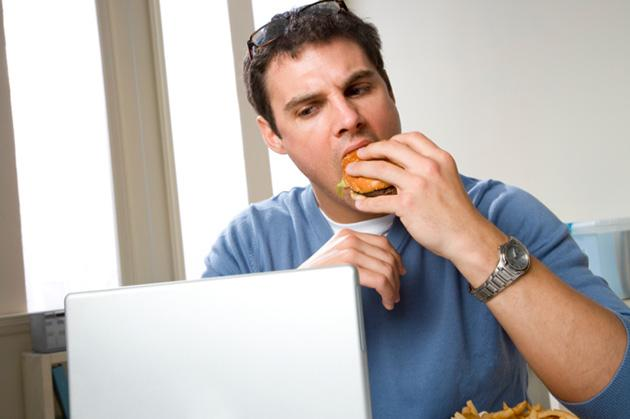 man eating sandwich in front of laptop