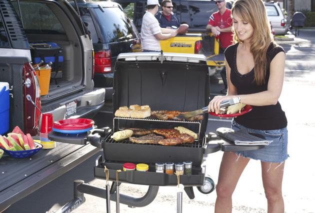Woman cooks with grill at tailgating party