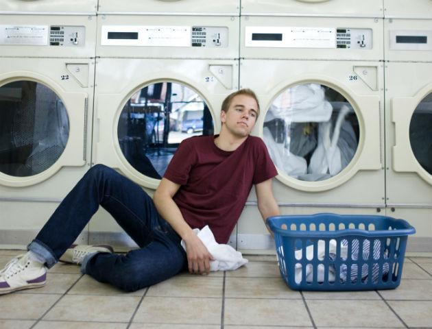 young man doing laundry in laundromat