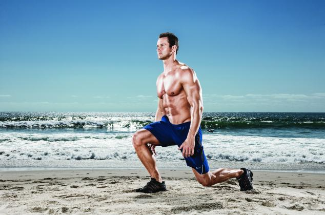 Muscular man doing lunges on the beach.