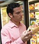 man reading nutrition label on frozen food