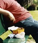obese man eating fatty fast food on a park bench