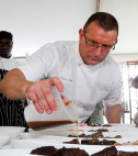 Robert Irvine pouring sauce on food