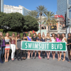 Group of swimsuit models holding swimsuit blvd sign in Las Vegas